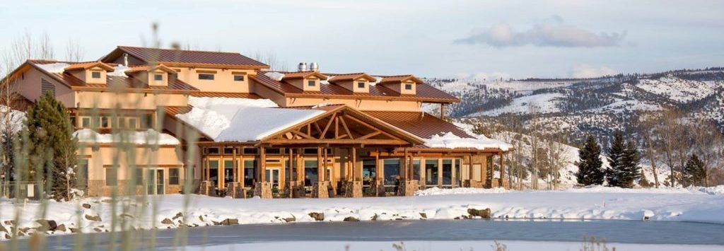 Snowy view of the Rio Grand Club and Resort hospitality location with mountains in the background and a frozen lake.