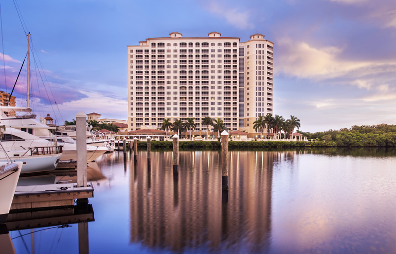 View of Cape Coral Resort hospitality location from the bay with boats and water in the foreground.