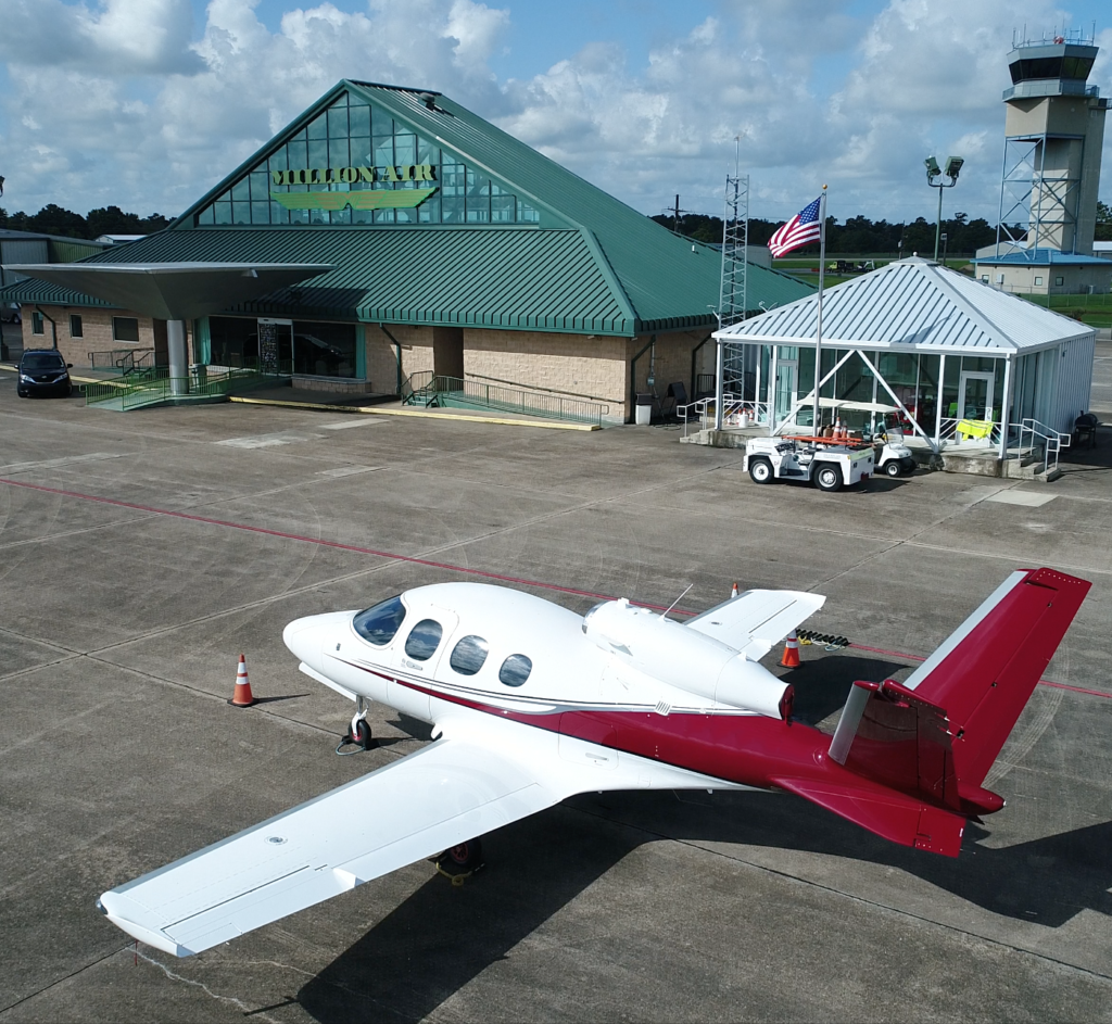 Aerial view of Million Air Lake Charles ramp and building with small aircraft in the foreground.